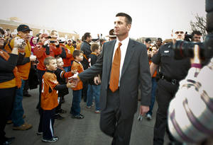 Photo - Cowboy head coach Mike Gundy greets the fans as he takes part in the team's pre-game walk before the Bedlam college football game between the University of Oklahoma Sooners (OU) and the Oklahoma State University Cowboys (OSU) at Boone Pickens Stadium in Stillwater, Okla., Saturday, Nov. 27, 2010. Photo by Chris Landsberger, The Oklahoman