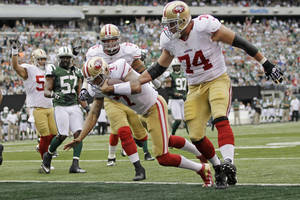 photo -   San Francisco 49ers quarterback Colin Kaepernick (7) rushes for a touchdown during the first half of an NFL football game as New York Jets inside linebacker Bart Scott (57) looks on Sunday, Sept. 30, 2012, in East Rutherford, N.J. (AP Photo/Kathy Willens)  