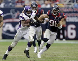 Photo - Minnesota Vikings running back Adrian Peterson (28) rushes for a gain as Houston Texans' Connor Barwin (98) pursues during the third quarter of an NFL football game Sunday, Dec. 23, 2012, in Houston. (AP Photo/Patric Schneider)