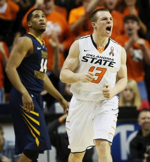 photo - Oklahoma State's Phil Forte (13) reacts in front of West Virginia's Gary Browne (14) after hitting a 3-point shot during an NCAA men's basketball game between Oklahoma State University (OSU) and West Virginia at Gallagher-Iba Arena in Stillwater, Okla., Saturday, Jan. 26, 2013. Photo by Nate Billings, The Oklahoman