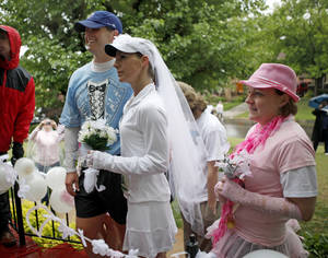 Photo - Joel Rogalsky and Amy Wills beside maid of honor Polly Price get married during the Oklahoma City Memorial Marathon on NW 35th, Sunday, May 1, 2011. Photo by Bryan Terry, The Oklahoman