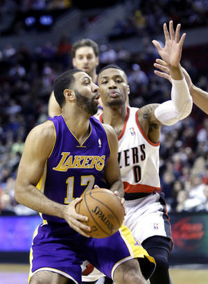 Photo - Los Angeles Lakers guard Kendall Marshall, left, looks to shoot against Portland Trail Blazers guard Damian Lillard during the first half of an NBA basketball game in Portland, Ore., Monday, March 3, 2014. (AP Photo/Don Ryan)