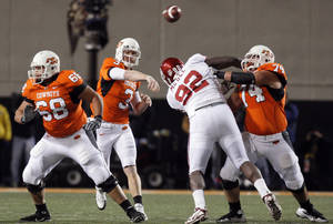 Photo - OSU quarterback Brandon Weeden (3) passes the ball as Grant Garner (74) blocks OU's Stacy McGee (92) and OSU's Lane Taylor (68) adds protection during the Bedlam college football game between the University of Oklahoma Sooners (OU) and the Oklahoma State University Cowboys (OSU) at Boone Pickens Stadium in Stillwater, Okla., Saturday, Nov. 27, 2010. Photo by Nate Billings, The Oklahoman ORG XMIT: KOD