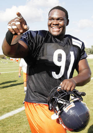 Photo - Chicago defensive tackle Tommie Harris, who played at OU, points to fans during training camp at Olivet Nazarene University in Bourbonnais, Ill., Friday. Harris is not fully participating in practice due to injuries. AP PHOTO