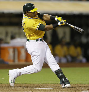 Photo - Oakland Athletics' Yoenis Cespedes swings for a two run triple off Los Angeles Angels' Joe Smith in the seventh inning of a baseball game Saturday, May 31, 2014, in Oakland, Calif. (AP Photo/Ben Margot)