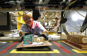 photo - Yolanda Holden places a completed order onto a conveyor belt prior to packaging at the Amazon.com 1.2 million square foot fulfillment center Monday, Nov. 26, 2012, in Phoenix. Americans clicked away on their computers and smartphones for deals on Cyber Monday, which is expected to be the biggest online shopping day in history. Shoppers are expected to spend $1.5 billion on Cyber Monday, up 20 percent from last year, according to research firm comScore. That would not only make it the biggest online shopping day of the year, but the biggest since comScore started tracking shoppers' online buying habits in 2001. (AP Photo/Ross D. Franklin) ORG XMIT: AZRF105