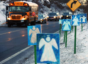 photo - A bus traveling from Newtown, Conn., to Monroe stops in front of 26 angels along the roadside on the first day of classes for Sandy Hook Elementary School students since the Dec. 14 shooting, in Monroe, Conn., Thursday, Jan. 3, 2013. Chalk Hill School in Monroe was overhauled especially for the students from the Sandy Hook School shooting. (AP Photo/Jessica Hill)