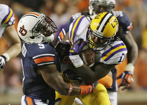 photo -   LSU running back Spencer Ware (11) pulls away from Auburn defensive back Jermaine Whitehead (9) in the first half of an NCAA college football game Saturday, Sept. 22, 2012 at Jordan-Hare Stadium in Auburn, Ala. (AP Photo/Dave Martin)