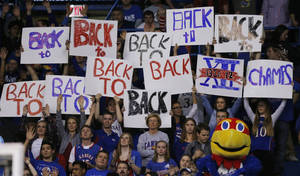 Photo - Kansas fans celebrate gaining a share of their tenth straight Big-12 championship during the second half of an NCAA college basketball game against Oklahoma in Lawrence, Kan., Monday, Feb. 24, 2014. Kansas defeated Oklahoma 83-75. (AP Photo/Orlin Wagner)