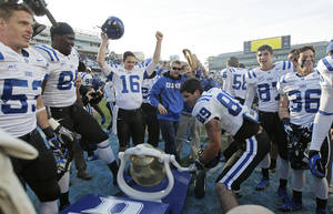 Photo - Duke's Braxton Deaver (89) rings the victory bell with teammates following Duke's 27-25 win over North Carolina in an NCAA college football game in Chapel Hill, N.C., Saturday, Nov. 30, 2013. (AP Photo/Gerry Broome)