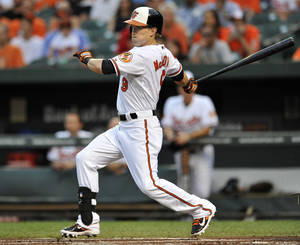 Photo - Baltimore Orioles' Nate McLouth follows through with a single against the Tampa Bay Rays in the first inning of a baseball game, Wednesday, Aug. 21, 2013 in Baltimore.(AP Photo/Gail Burton)