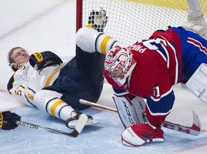 Photo - Buffalo Sabres' Tyler Myers collides with Montreal Canadiens goaltender Carey Price during the third period of an NHL hockey game Tuesday, March 25, 2014, in Montreal. Montreal won 2-0. (AP Photo/The Canadian Press, Graham Hughes)