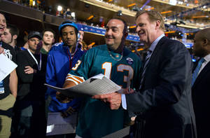 Photo - Giovanni Estevez, center, of Miami, poses for a photo with NFL Commissioner Roger Goddell during the fourth through seventh rounds of the NFL Draft, Saturday, April 27, 2013 at Radio City Music Hall in New York. Estevez, a member of the Miami Dolphins' Fins fan club, also announced two draft picks for the Dolphins. (AP Photo/Craig Ruttle)