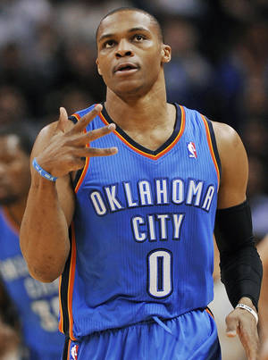 Photo - Oklahoma City Thunder guard Russell Westbrook celebrates a 3-point basket during the first half of an NBA basketball game against the San Antonio Spurs, Saturday, Dec. 21, 2013, in San Antonio. (AP Photo/Darren Abate)