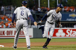 Photo -   Tampa Bay Rays' B.J. Upton, right, high-fives third base coach Tom Foley as he rounds the bases after hitting a solo home run in the first inning of a baseball game against the Baltimore Orioles in Baltimore, Wednesday, Sept. 12, 2012. (AP Photo/Patrick Semansky)