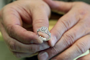 Photo - In this May 14, 2014 photo, Brad Padgett, owner of Bradley's Jewelers, shows off one of his favorite engagement rings in Jacksonville, N.C.  The answer to the question of how much to spend on an engagement ring rests in striking a balance between a ring that will dazzle your beloved without tarnishing your future financial goals together. (AP Photo/The Daily News, Maria Sestito)