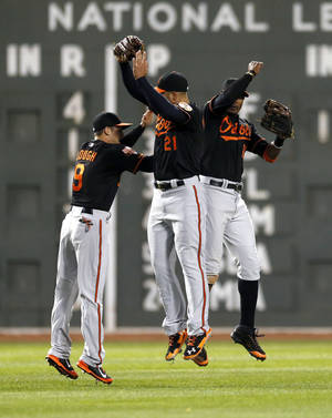 Photo - Baltimore Orioles' David Lough (9), Nick Markakis (21) and Adam Jones (10) celebrate the team's 8-4 win overthe Boston Red Sox in a baseball game in Boston, Friday, April 18, 2014. (AP Photo/Michael Dwyer)
