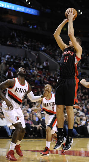 Photo - Toronto Raptors' Jonas Valanciunas (17) shoots against Portland Trail Blazers defenders J.J. Hickson, left, and Damian Lillard (0) during the first half of an NBA  basketball game in Portland, Ore., Monday, Dec. 10, 2012. (AP Photo/Greg Wahl-Stephens)