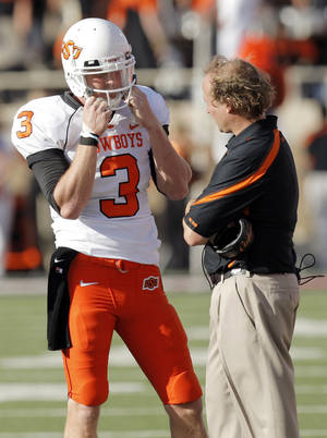 Photo - OSU quarterback Brandon Weeden (3) talks to offensive coordinator Dana Holgorsen during the college football game between the Oklahoma State University Cowboys and Texas Tech University Red Raiders at Jones AT&T Stadium in Lubbock, Texas, Saturday, October 16, 2010. OSU won, 34-17. Photo by Nate Billings, The Oklahoman ORG XMIT: KOD