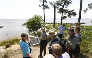 Photo - In this Thursday June 5, 2014 photo, US Secretary of the Interior Sally Jewell, left, tours Jamestown Island in Jamestown, Va. Jewell toured Jamestown to highlight climate change's threat to the first permanent European settlement in America.  A power company's plan to build high-rise transmission towers within sight of Jamestown Island has stirred opposition from historic preservationists who say they'll be a visual blight from the swampy shore where America sprouted. (AP Photo/Steve Helber)