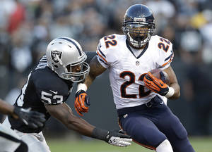 Photo - Chicago Bears running back Matt Forte (22) carries against Oakland Raiders linebacker Nick Roach (53) during the first quarter of an NFL preseason football game in Oakland, Calif., Friday, Aug. 23, 2013. (AP Photo/Marcio Jose Sanchez)