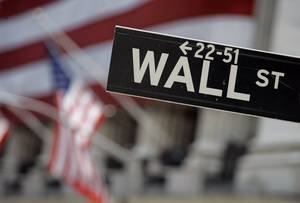 Photo - FILE - In this May 11, 2007, file photo, a Wall Street sign is mounted near the flag-draped facade of the New York Stock Exchange. U.S. stocks are dropping in early trading amid financial jitters in Europe and disappointing retail earnings. (AP Photo/Richard Drew, File)