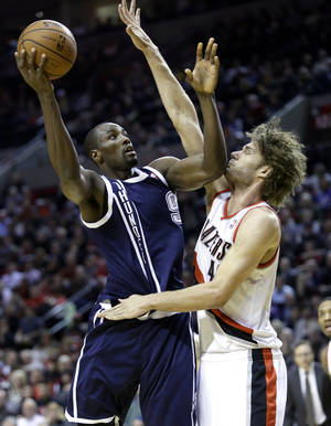 Photo - OKC's Serge Ibaka, left, shoots against Portland's Robin Lopez during first-half action on Tuesday night. AP Photo