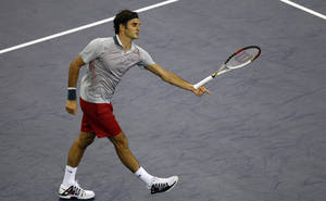 Photo - Switzerland's Roger Federer tosses his racket during a match against France's Gael Monfils for the Shanghai Masters tennis tournament at the Qizhong Forest Sports City Tennis Center in Shanghai, China, Thursday, Oct. 10, 2013. Monfils won 6-4, 6-7, 6-3.  (AP Photo)