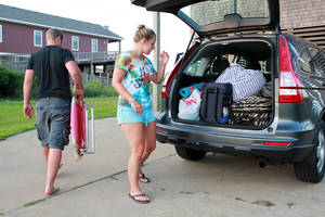Photo - Nicole Specht, and and Ryan Witman, pack their Honda CRV heading back home to Lancaster Pa., before dawn on Thursday, July 3, 2014, during a mandatory evacuation, in Rodanthe, N.C. Arthur strengthened to a hurricane early Thursday and threatened to give North Carolina a glancing blow on Independence Day, prompting a stream of vacationers and residents to head home from some parts of the state's popular but flood-prone Outer Banks. (AP Photo/Jerome Bailey Jr.)