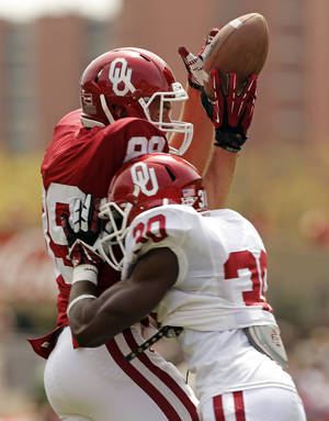 Photo - Connor Knight is hit just as he touches a pass by Thaddeus LaGrone during the Spring College Football Game of the University of Oklahoma Sooners (OU) at Gaylord Family-Oklahoma Memorial Stadium in Norman, Okla., on Saturday, April 12, 2014.  The pass was incomplete.  Photo by Steve Sisney, The Oklahoman
