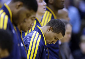 Photo - Indiana Pacers' George Hill pauses during a moment of silence for those who were killed and injured in the Connecticut elementary school shooting before an NBA basketball game against the Philadelphia 76ers, Friday, Dec. 14, 2012, in Indianapolis. (AP Photo/Darron Cummings)