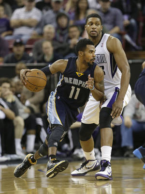 Photo - Memphis Grizzlies guard Mike Conley, left, drives against Sacramento Kings forward Rudy Gay during the third quarter of an NBA basketball game in Sacramento, Calif., Wednesday, Jan. 29, 2014.  The Grizzlies won 99-89.(AP Photo/Rich Pedroncelli)