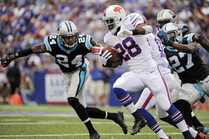 Photo - Buffalo Bills running back C.J. Spiller (28) runs the ball against Carolina Panthers cornerback Josh Norman (24) in the second quarter of an NFL football game Sunday, Sept. 15, 2013, in Orchard Park, N.Y. (AP Photo/Gary Wiepert)
