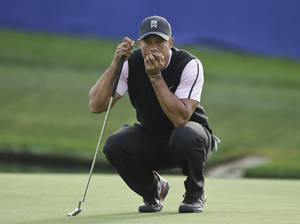 Photo - Tiger Woods examines his putt while waiting for his playing partners on the 18th green of the South Course at Torrey Pines during the first round of the Farmers Insurance Open golf tournament Thursday, Jan. 23, 2014, in San Diego.  (AP Photo/Lenny Ignelzi)