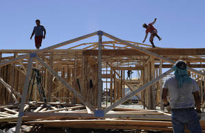 Photo - FILE - In this Sept. 24, 2013, file photo, a man steadies himself as he and others work on framing new houses, in Odessa, Texas. America's energy boom is fueling population growth west of the Mississippi River. New 2013 census information released Thursday, March 27, 2014, showed that six of the 10 fastest-growing metropolitan areas and eight of the 10 fastest-growing counties in the country are located in or near the oil- and gas-rich fields of the Great Plains and Mountain West. More and more oil and gas drilling is being done in those regions, drawing people from around the nation looking for work, the Census Bureau said. Neighboring cities Odessa and Midland, Texas, show up as the second and third fastest-growing metro areas in the country. (AP Photo/Pat Sullivan, File)