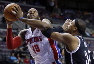 Photo - Detroit Pistons center Greg Monroe (10) tries to go to the basket against Brooklyn Nets forward Paul Pierce, right, during the first half of an NBA basketball game on Friday, Feb. 7, 2014, in Auburn Hills, Mich. (AP Photo/Duane Burleson)