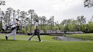 Photo - Bubba Watson walks with his Ted Scott down the 15th fairway during the second round of the Masters golf tournament Friday, April 11, 2014, in Augusta, Ga. (AP Photo/David J. Phillip)