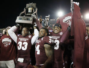 Photo - Mississippi State players Kivon Coman (33), Josh Robinson (34) and Michael Hodges, right, celebrate with the trophy after beating Rice in the Liberty Bowl NCAA college football game Tuesday, Dec. 31, 2013, in Memphis, Tenn. Mississippi State won 44-7. (AP Photo/Mark Humphrey)