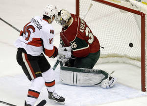 Photo - Ottawa Senators' Clarke MacArthur, left, scores a power play goal against Minnesota Wild goalie Darcy Kuemper in the first period of an NHL hockey game, Tuesday, Jan. 14, 2014, in St. Paul, Minn. (AP Photo/Jim Mone)