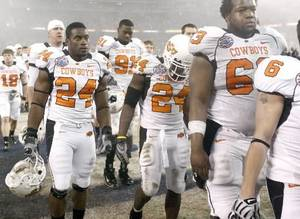 Photo - Deron Fontenot, left, Kendall Hunter, and David Washington of OSU walk off the field after their loss during the Holiday Bowl college football between Oklahoma State and Oregon at Qualcomm Stadium in San Diego, Tuesday, Dec. 30, 2008. PHOTO BY BRYAN TERRY, THE OKLAHOMAN. ORG XMIT: KOD