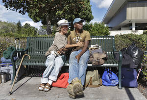 Photo - In a Friday, Jan. 11, 2013 photo, Cindy Edlund, left, and James Franklin Jr., both of whom are homeless, spend the day on a bench outside the Sarasota City Hall Friday, Jan. 11, 2013, in Sarasota, Fla. Newer, wealthy residents in the Gulf Coast city known for its arts scene and beautiful beaches are buying expensive downtown condos so they can live an urban lifestyle _ but don't want the problems associated with a city, including the 700 or so homeless people who inhabit the county, the American Civil Liberties Union and others contend. (AP Photo/Chris O'Meara)