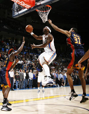 Photo - Oklahoma City's Chris Wilcox (54) tries to score between Anthony Morrow (22) and Brandan Wright (32) of Golden State Warriors during the NBA basketball game between the Golden State Warriors and the Oklahoma City Thunder at the Ford Center in Oklahoma City, Monday, December 8, 2008. BY NATE BILLINGS, THE OKLAHOMAN