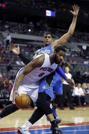 Photo - Detroit Pistons center Andre Drummond (0) drives to the basket against Orlando Magic forward Tobias Harris during the first half of an NBA basketball game Tuesday, Jan. 28, 2014, in Auburn Hills, Mich. (AP Photo/Duane Burleson)