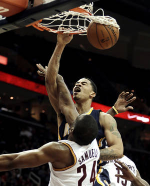 Photo - Indiana Pacers' Gerald Green, top, dunks the ball against Cleveland Cavaliers' Samardo Samuels during the fourth quarter of an NBA basketball game on Friday, Dec. 21, 2012, in Cleveland. The Pacers won 99-89. (AP Photo/Tony Dejak)