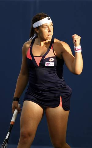 Photo - Marion Bartoli, from France, reacts during a match against Simona Halep, from Romania, at the Western & Southern Open tennis tournament, Wednesday, Aug. 14, 2013, in Mason, Ohio. (AP Photo/David Kohl)