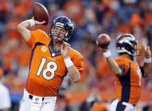Photo - Denver Broncos quarterback Peyton Manning (18) warms up prior to the Broncos' NFL football game against the Baltimore Ravens, Thursday, Sept. 5, 2013, in Denver. (AP Photo/Jack Dempsey)