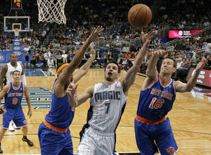 photo - FILE - In this Nov. 13, 2012 file photo,Orlando Magic&#039;s J.J. Redick (7) goes up for a shot between New York Knicks&#039; Steve Novak (16) and Rasheed Wallace, left, during the first half of an NBA basketball game in Orlando, Fla. A person familiar with the situation says the Orlando Magic have agreed to trade veteran shooting guard Redick, center Gustavo Ayon and reserve point guard Ish Smith to the Milwaukee Bucks in exchange for guards Doron Lamb and Beno Udrih, as well as forward Tobias Harris. The person spoke to The Associated Press Thursday, Feb. 21, 2013 on condition of anonymity because the deal was not officially complete. (AP Photo/John Raoux, FIle)