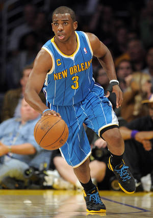 Photo -   FILE - In this April 26, 2011, file photo, New Orleans Hornets guard Chris Paul drives the ball downcourt during the first half in Game 5 of a first-round NBA basketball playoff series against the Los Angeles Lakers in Los Angeles. The framework of a three-team trade is in place to send Paul to the Los Angeles Lakers pending details of the transaction still being worked on Thursday, Dec. 8, 2011, according to a person familiar with the negotiations. (AP Photo/Mark J. Terrill, File)