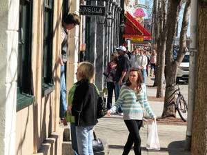 Photo - Visitors crowd Market Street in downtown Charleston, S.C., on Friday, Feb.15, 2013. The Southeastern Wildlife Exposition is being staged in Charleston  this weekend, a weekend that serves as the unofficial start to the spring tourism season in South Carolina. (AP Photo/Bruce Smith, file)