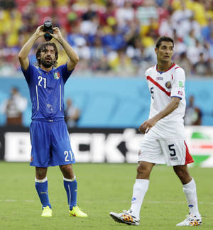 Photo - Costa Rica's Celso Borges, right, waits for play to resume as Italy's Andrea Pirlo cools off with water during the group D World Cup soccer match between Italy and Costa Rica at the Arena Pernambuco in Recife, Brazil, Friday, June 20, 2014.  (AP Photo/Ricardo Mazalan)